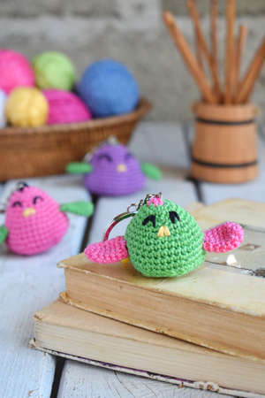 Colored crochet bird. The toy for babies or trinket. Handmade gift. DIY crafts concept.