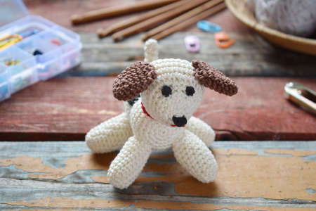 Making crochet white dog. The toy for babies or trinket. On the table threads, needles, hook, cotton yarn. Handmade gift. DIY crafts concept.