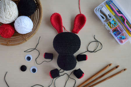 Making crochet voodoo rabbit. Toy for Halloween. On table threads, hook, cotton yarn. Handmade gift. Mystic, occult, horror DIY crafts concept. Step 1 - knit all details of toy.