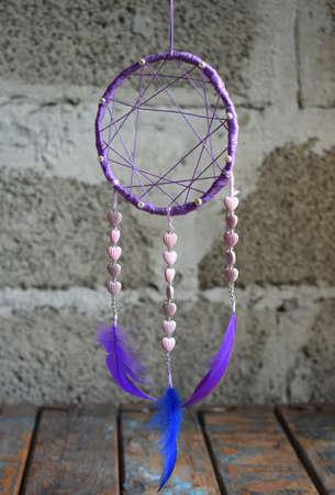 Purple dream catcher on grey background. The dreamcatcher decoration accessory for bedroom, closeup photo. Workshop, hobby, handicraft, creativity concept.