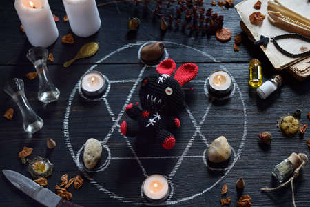 In Voodoo rabbit are needles pricked. Candles, pentagram, stones, love potion and old books on witch table. Occult, esoteric or divination concept. The mystic, Halloween and vintage background Фото со стока
