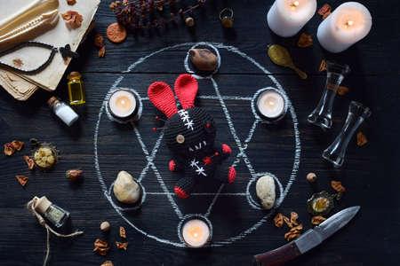 En conejo vudú se pinchan agujas. Velas, pentagrama, piedras, poción de amor y libros antiguos sobre la mesa de brujas. Concepto oculto, esotérico o adivinatorio. El fondo místico, Halloween y vintage.