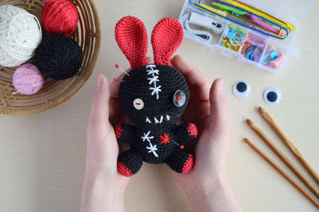 Making crochet voodoo rabbit. Toy for Halloween. On table threads, hook, cotton yarn. Handmade gift. Mystic, occult, horror DIY crafts concept. 写真素材