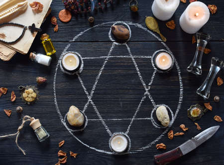 The pentagram circle with candles, stones, love potion and old books on witch table. Occult, esoteric or divination concept. Mystic, Halloween and vintage background