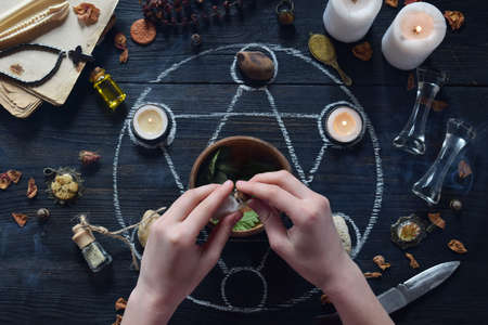 The womens hands make love potion on pentagram circle with candles, stones and old books on witch table. Occult, esoteric or divination concept. Mystic, Halloween and vintage background