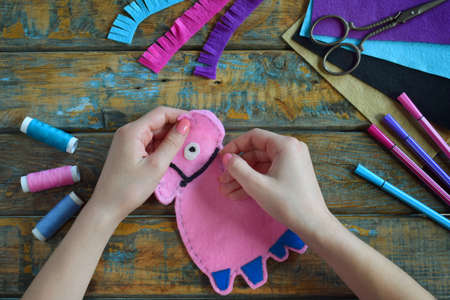 Making the pink lama. Sewing toys from felt with your own hands. DIY concept for children. Handmade crafts. Step 3. Sew all details of toy. 写真素材
