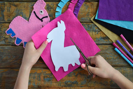 Making the pink lama. Sewing toys from felt with your own hands. DIY concept for children. Handmade crafts. Step 1. Circle the stencil of toy details.