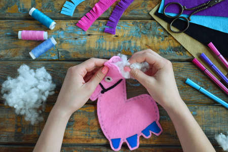 Making the pink lama. Sewing toys from felt with your own hands. DIY concept for children. Handmade crafts. Step 4. Stuff the toy with padding polyester.