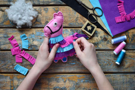 Making the pink lama. Sewing toys from felt with your own hands. DIY concept for children. Handmade crafts. Step 5. Decorate the toy.