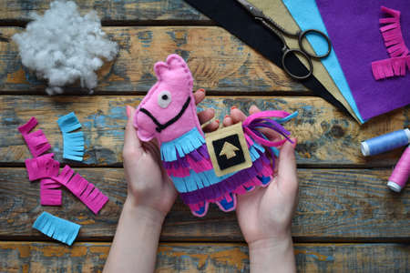 Making the pink lama. Sewing toys from felt with your own hands. DIY concept for children. Handmade crafts. Step 6. Finished toy.