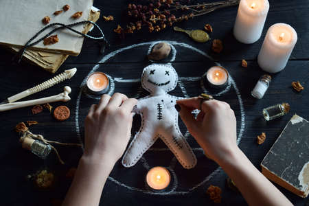 In Voodoo doll are needles pricked. The candles, pentagram, stones, love potion and old books on witch table. Occult, esoteric or divination concept. Mystic, Halloween and vintage background Фото со стока