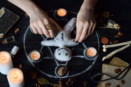 In Voodoo doll are needles pricked. The candles, pentagram, stones, love potion and old books on witch table. Occult, esoteric or divination concept. Mystic, Halloween and vintage background