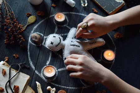 En muñeco vudú se pinchan agujas. Las velas, el pentagrama, las piedras, la poción de amor y los libros antiguos sobre la mesa de brujas. Concepto oculto, esotérico o adivinatorio. Fondo místico, Halloween y vintage Foto de archivo