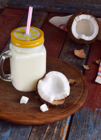 Coconut milk in bottle with broken coco on wooden background. Delicious milk cocktail. Copy space.