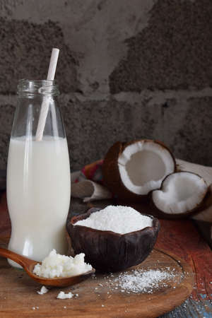 Coconut milk and oil with broken coco on wooden background. Delicious milk cocktail. Copy space.