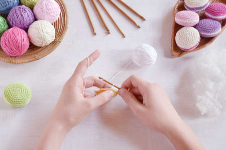 Making crochet amigurumi french macarons. The toy for babies or trinket. Threads, needles, hook, cotton yarn. Handmade gift. Income from hobby. DIY crafts concept. Step 1 - knit all details. Imagens