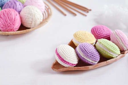 Crochet amigurumi french macarons. The toy for babies or trinket. Threads, needles, hook, cotton yarn. Handmade gift. Income from hobby. DIY crafts concept.