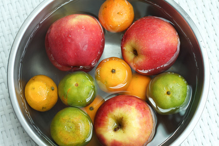 Cleaning fruit in the bowl with water