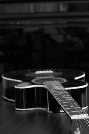 Acoustic Guitar In Black And White On The Table Photo