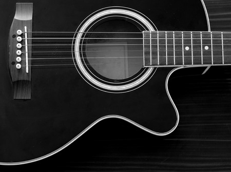 fingerboard: Acoustic Guitar in black and white on the table