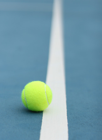 Yellow tennis ball on the blue courte photo