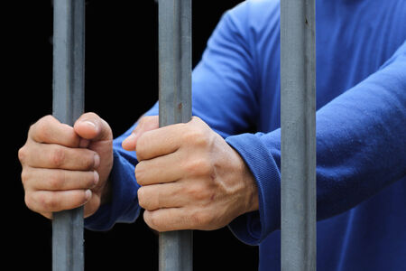waiting convict: Prisonner hand holding a metal bars Stock Photo