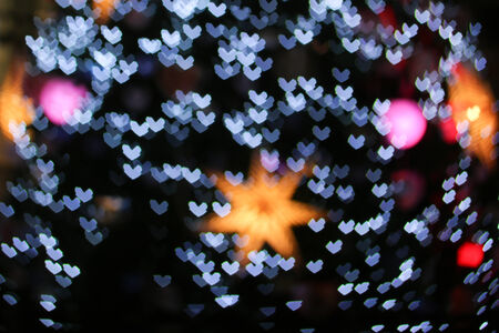 A colorful defocused of Christmas lights in love heart shape background photo