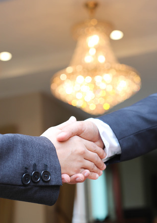 baby boomer: Business people shaking hands under chandelier