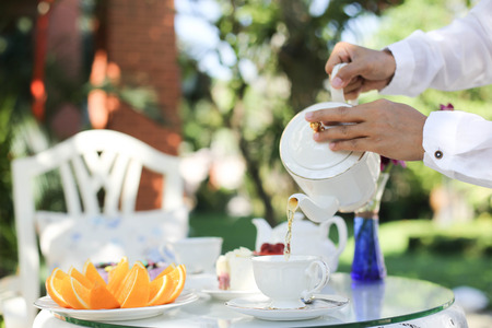 afternoon fancy cake: Afternoon tea with a man pouring tea from pot in to a cup