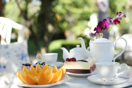 tazza di te: Un uomo con un tè pomeridiano e dolci e frutta arancione in giardino