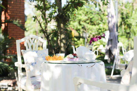 mimbre: Té de la tarde y pasteles y frutas de color naranja en el jardín