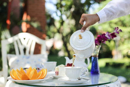 Afternoon tea with a man pouring tea from pot in to a cup