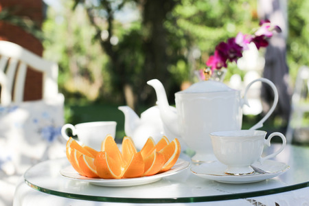 afternoon fancy cake: Afternoon tea and and fruit orange in the garden