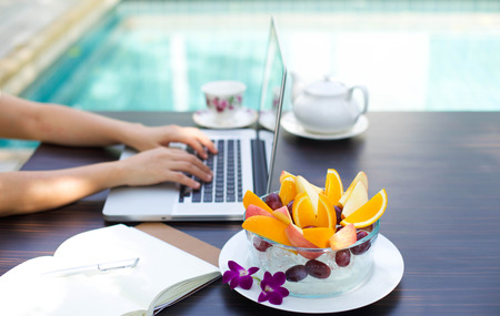 Business people working at home on laptop computer with blows of fresh fruit by swimming pool Archivio Fotografico