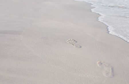 footprints on sandy beach and wave in Thailand photo