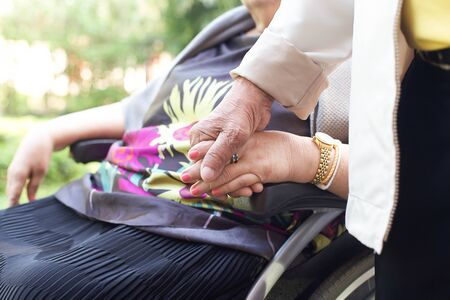Old people , husband holding his wife is hands while  she in a wheel chair Standard-Bild