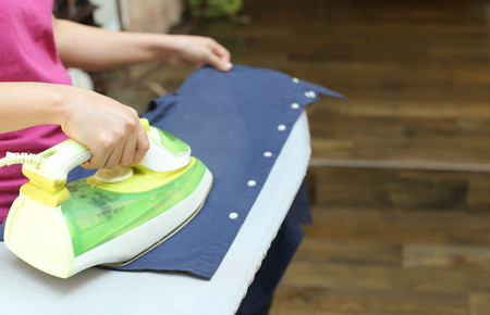 steam iron: Woman ironing a blue shirt with a steam iron in blur background Stock Photo
