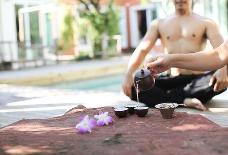 foe: Asian man doing a Yoga and a tea pot foe good health