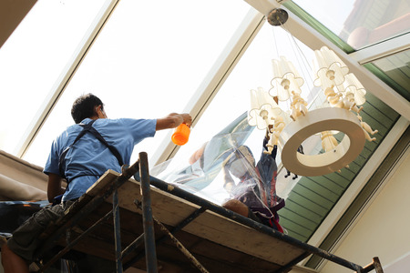 unidentified  people wrappers tinting a glass house window with a tinted foil or film using foggy spray