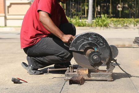 unidentified man using Steel cut machine cut a metal photo