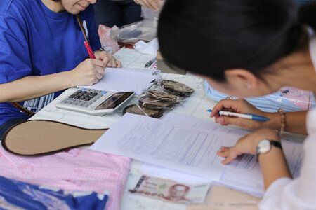 shorthand: business womans hand writing in paper for agreement with Thai currency Stock Photo