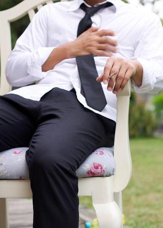 dolor de pecho: El hombre de negocios tiene dolor en el pecho por fumar un cigarrillo Foto de archivo