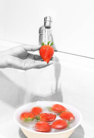 Woman Washing fresh Strawberries in the Kitchen Sink photo