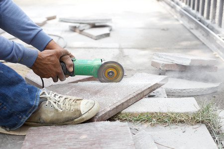 Grinder worker cuts a stone tile with electric tool photo