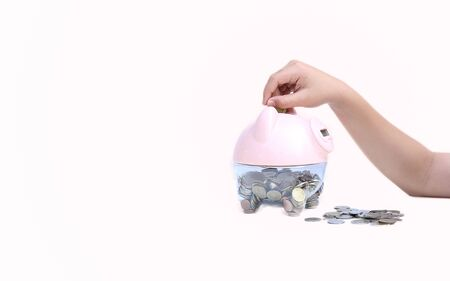 Education, school and money saving concept - Child putting coin into big piggy bank photo