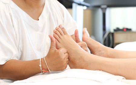 Receiving: woman receiving and relaxing foot massage at the health spa Stock Photo