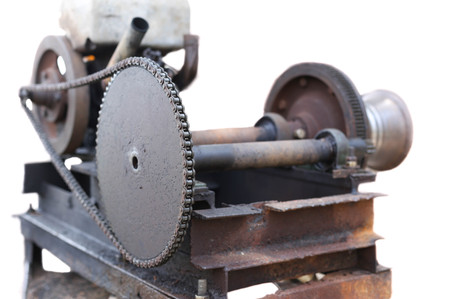 flywheel: Old and rusty engin with chain in white background
