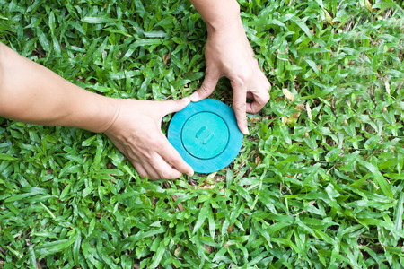 Pet control putting Termite bait system in to the ground in the blue lid stoping termite damage the house 스톡 콘텐츠
