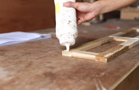 Carpenter putting glue on a piece ofcedar wood in blur background