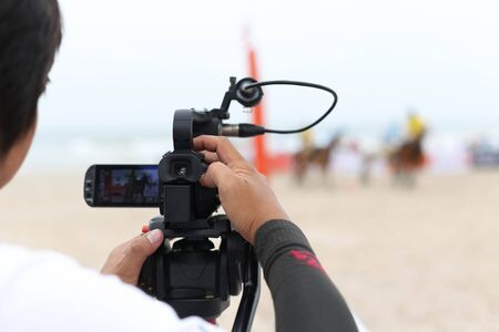 polo sport: Man holding camcorder as working recording on a beach Polo Tournament sport Stock Photo